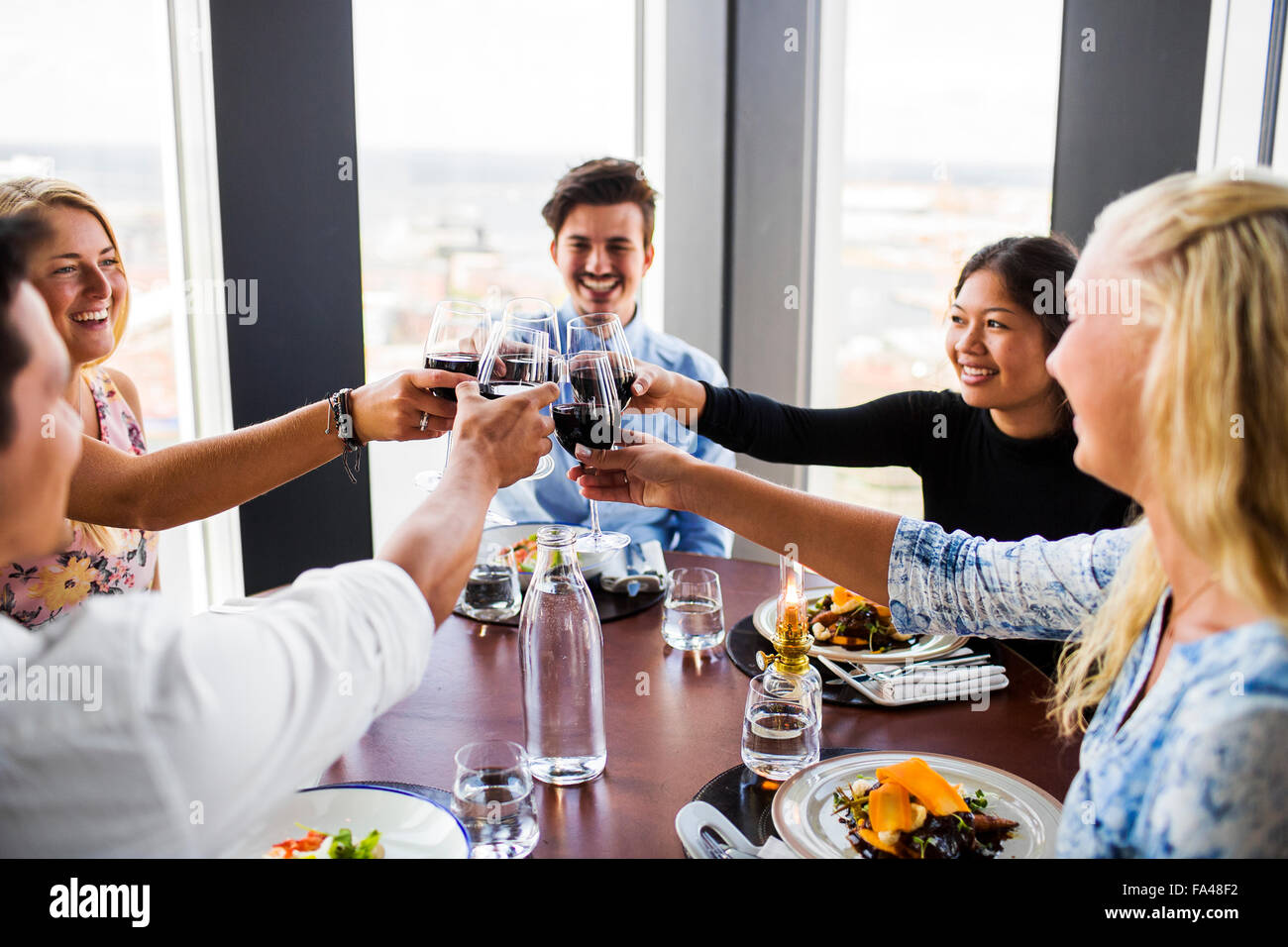 Friends toasting with red wine and enjoying at Sky bar restaurant - Stock Image