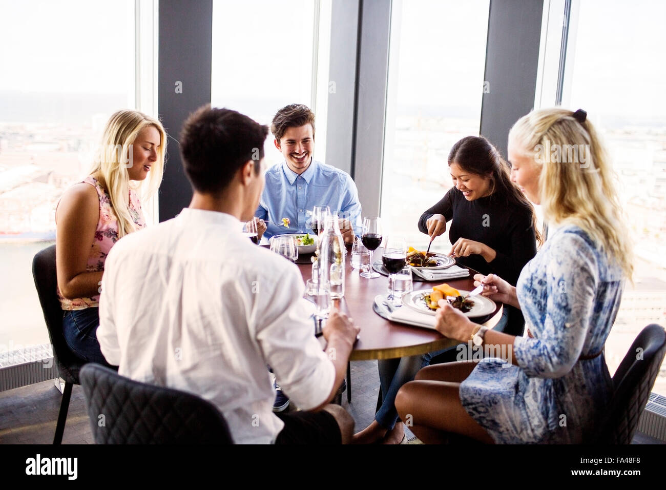 Happy friends having meal at Sky bar restaurant - Stock Image