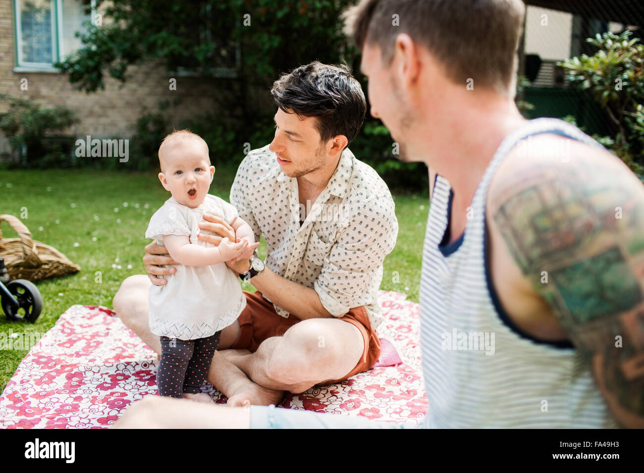 Gay couple looking at baby girl while sitting in yard - Stock Image