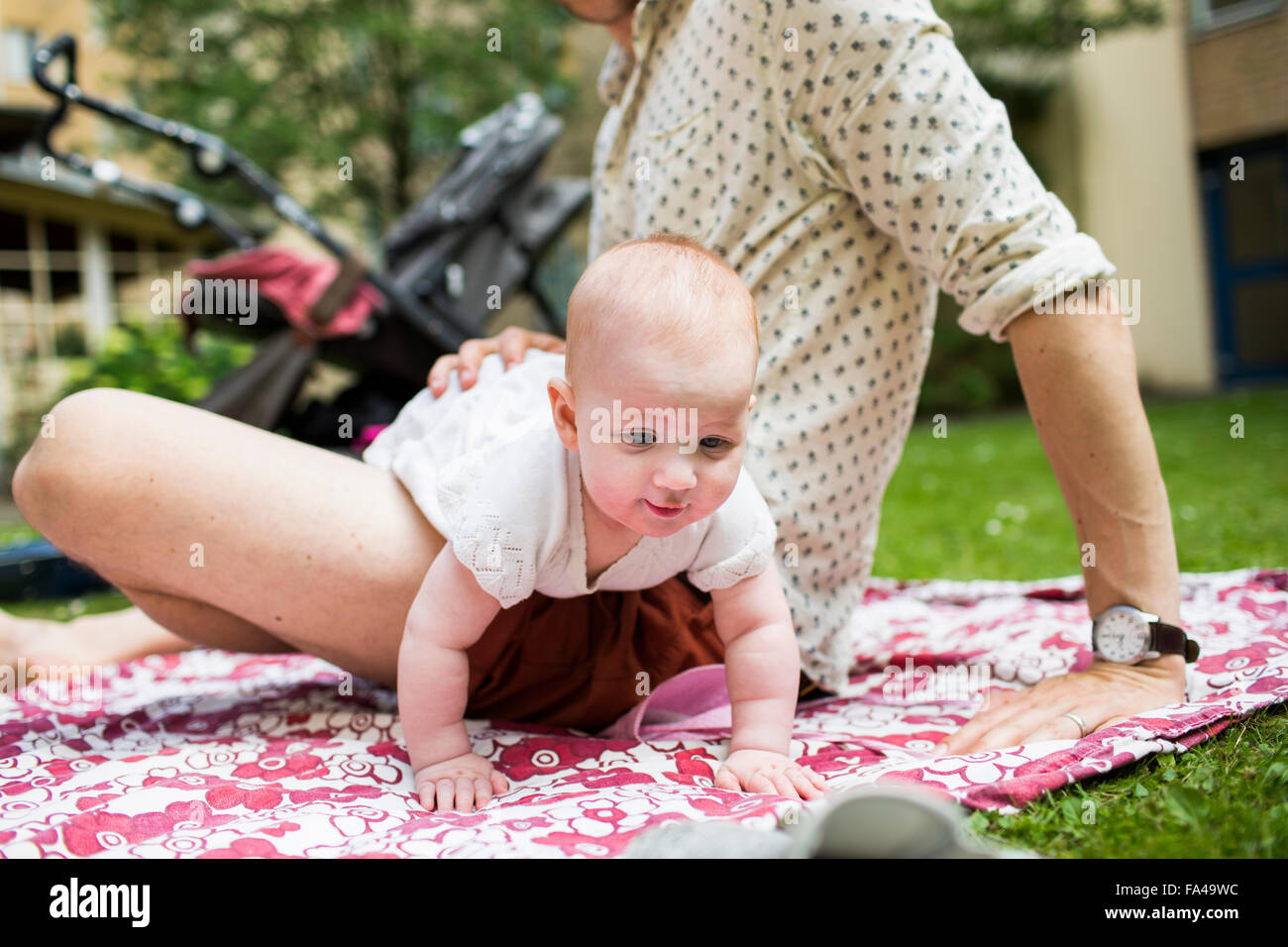 Baby girl lying on father's lap at yard - Stock Image