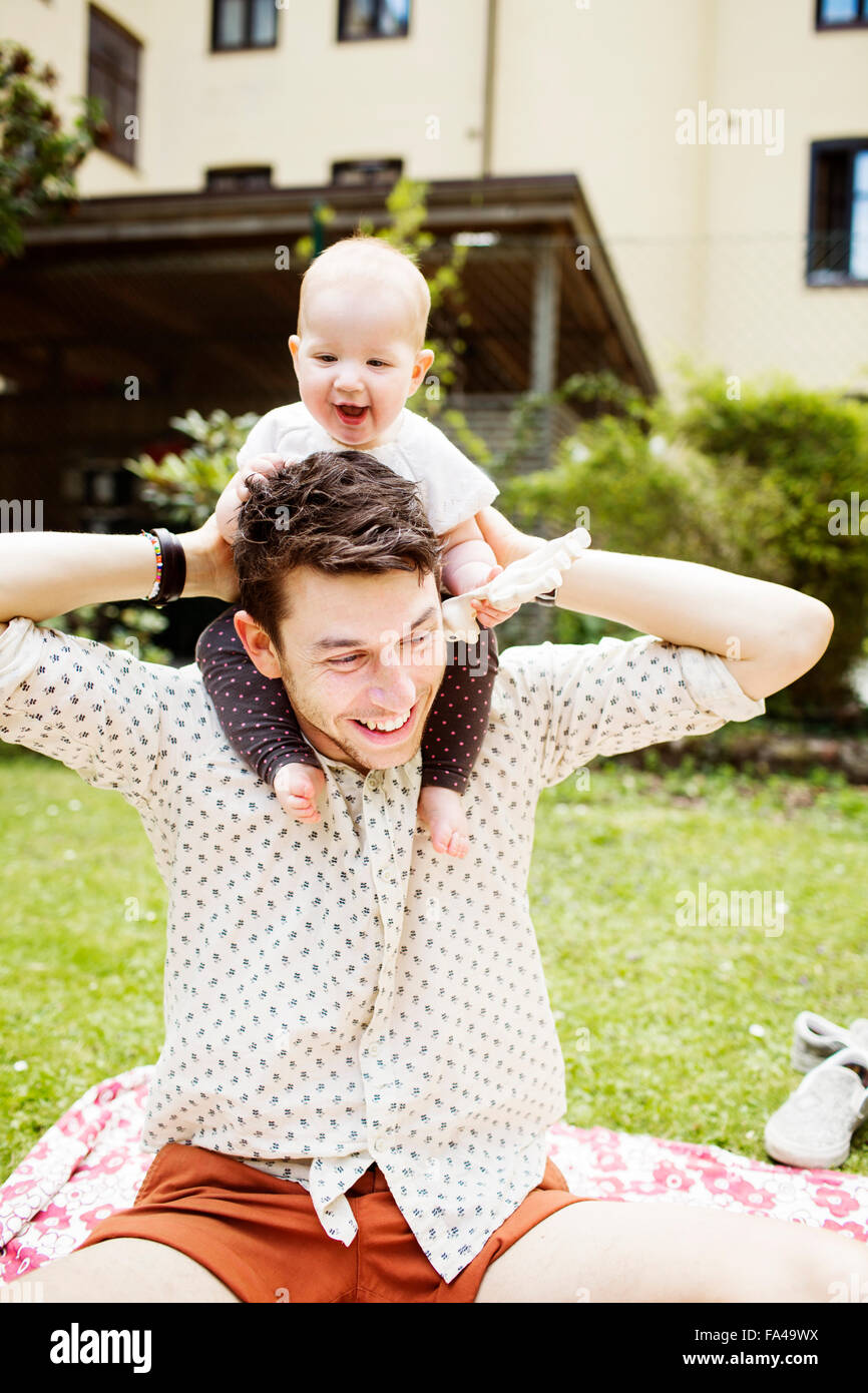 Happy father carrying baby girl on shoulders at yard Stock Photo