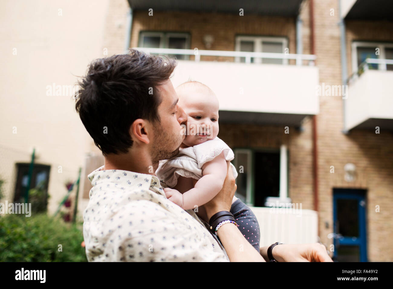 Loving father kissing baby girl outside building - Stock Image