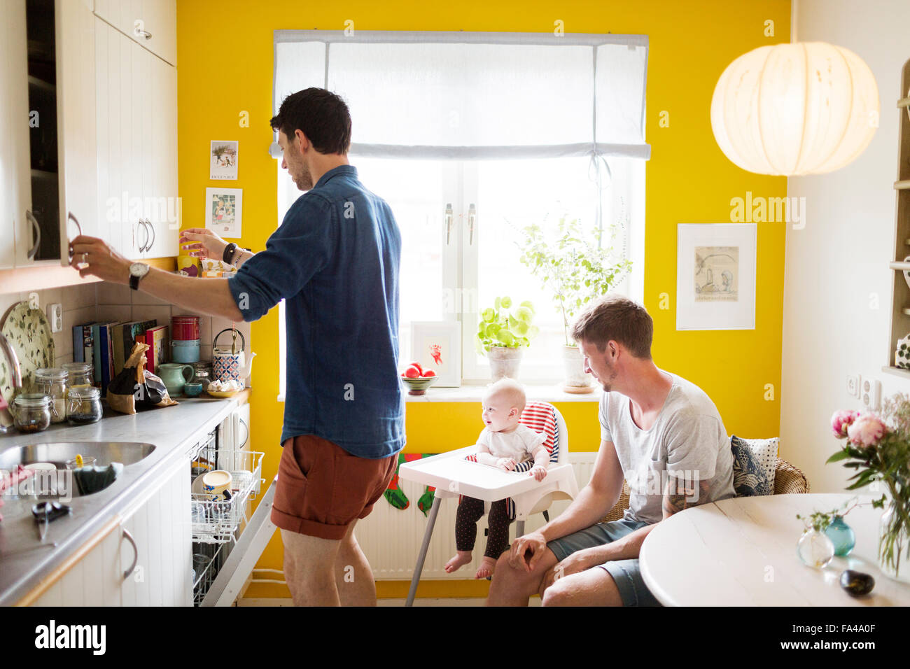 Gay couple with baby girl sitting on high chair in kitchen Stock Photo
