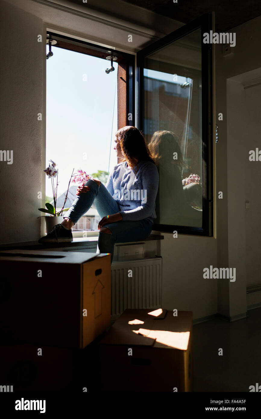 Thoughtful young woman sitting on window sill at new home - Stock Image