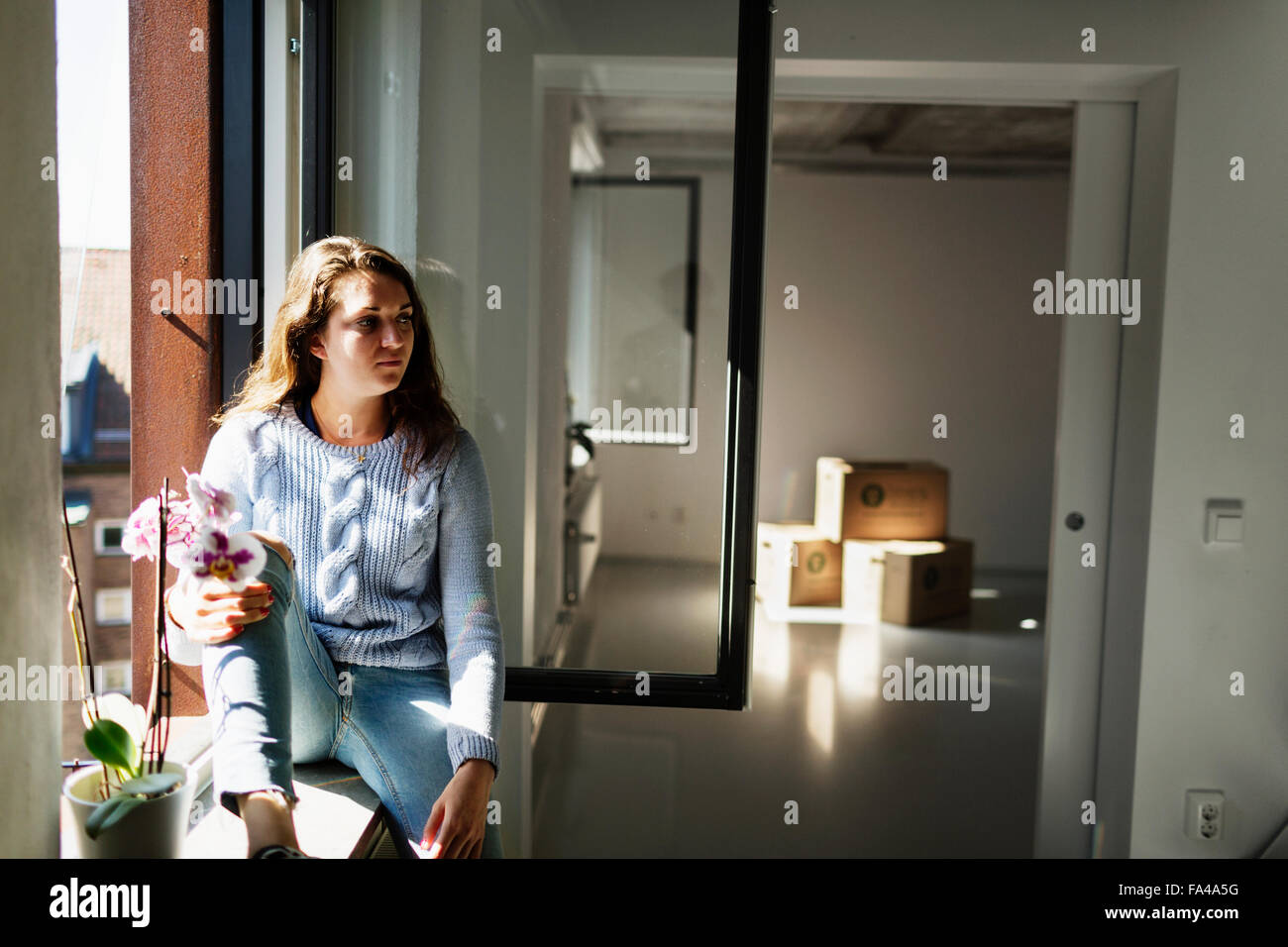 Thoughtful woman looking away sitting on window sill at new home - Stock Image