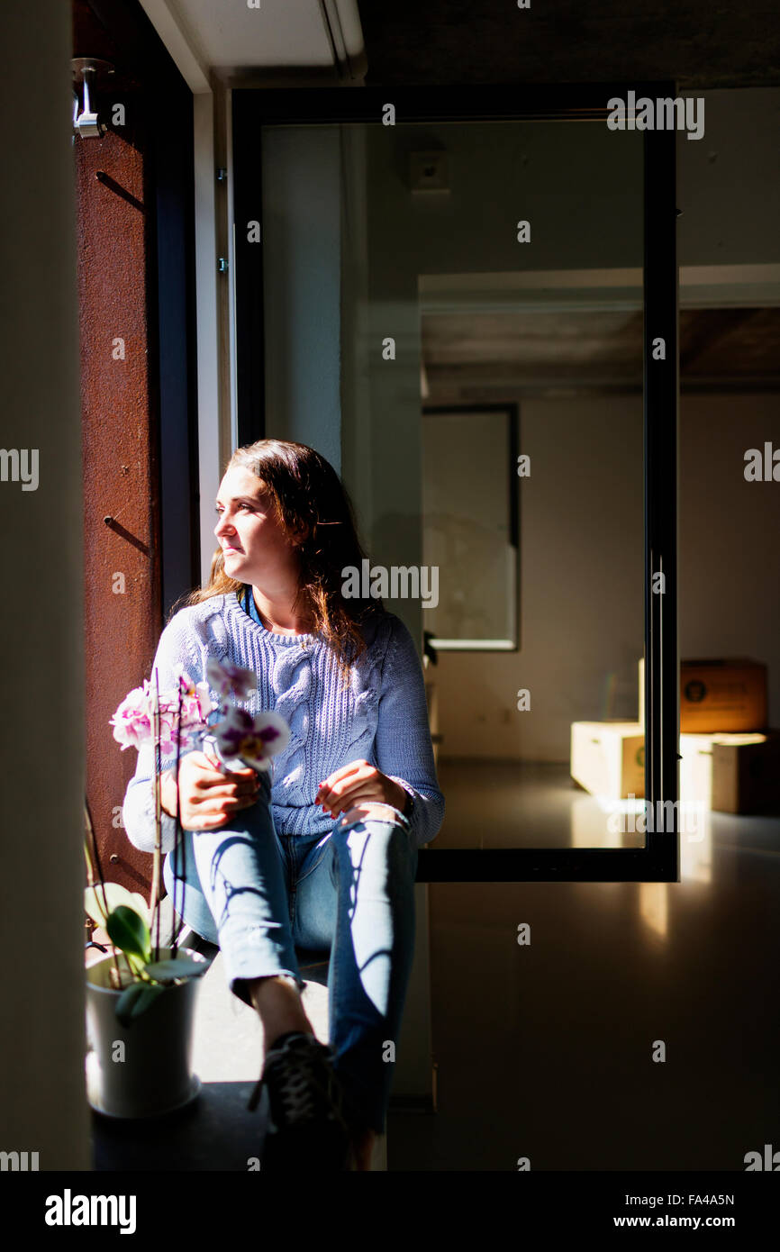 Full length of thoughtful young woman sitting on window sill Stock Photo