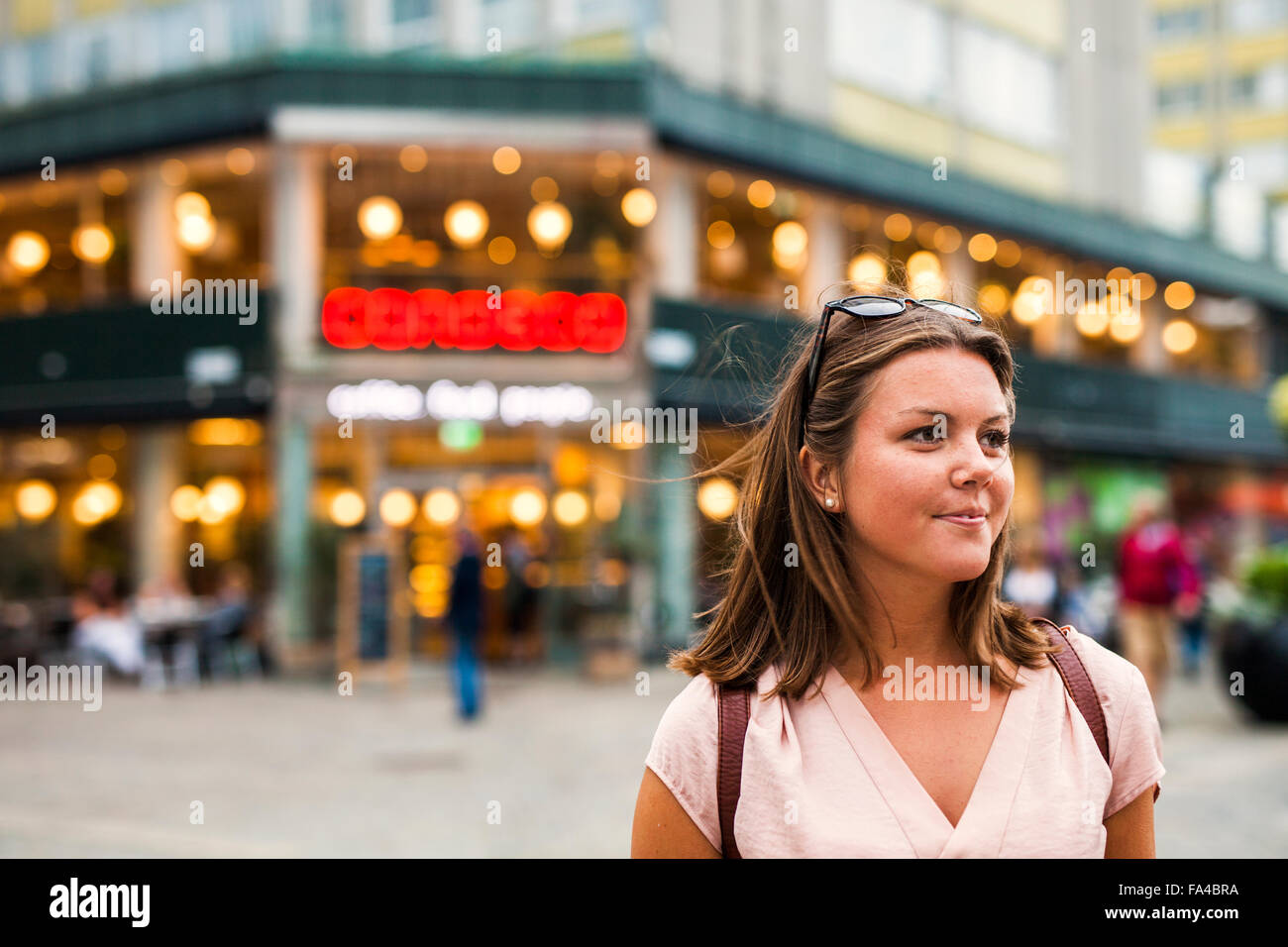 Beautiful woman looking away while standing in city - Stock Image