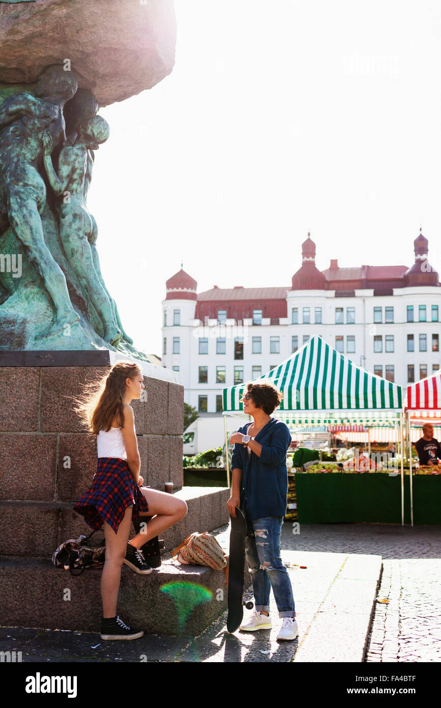 Female friends talking while standing by statue on street - Stock Image
