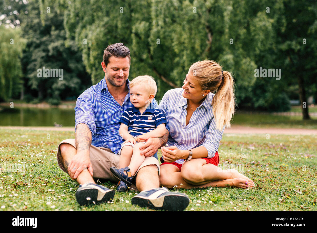 Parents watching son while sitting at park Stock Photo