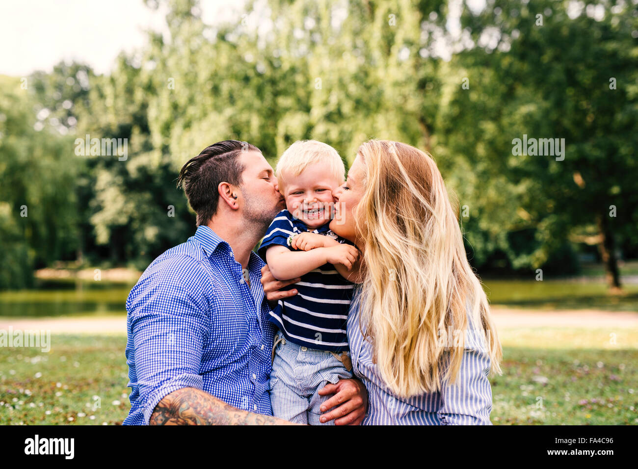 Parents kissing happy son - Stock Image