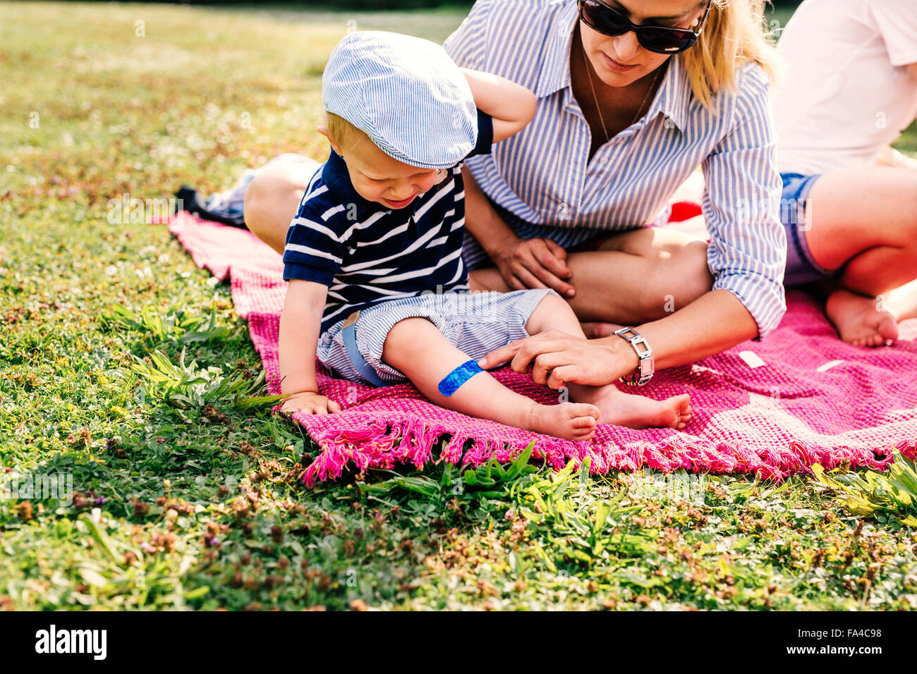 Mother putting bandage on son's leg during picnic in park - Stock Image