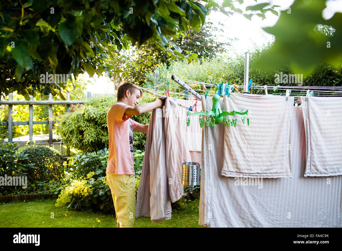 Teenage boy doing laundry work in garden - Stock Image