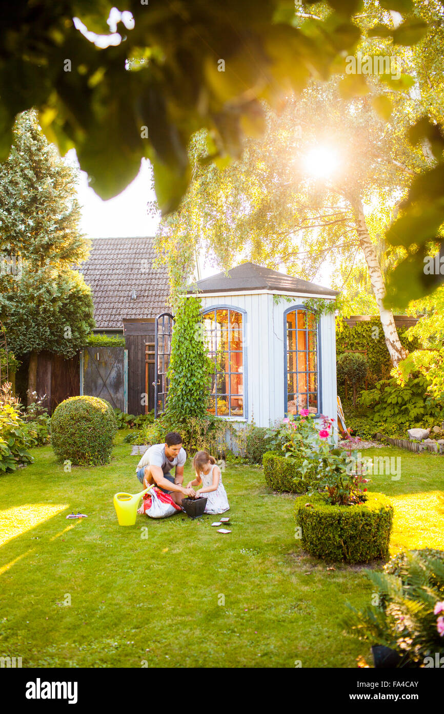 Father and daughter filling pot with soil in garden - Stock Image