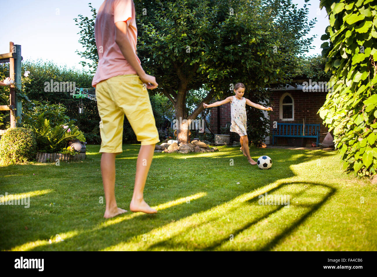 Brother And Sister Playing Soccer In Backyard