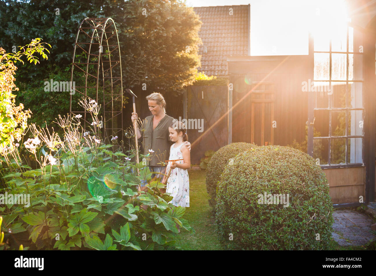 Happy mother and daughter with gardening equipment in backyard Stock ...