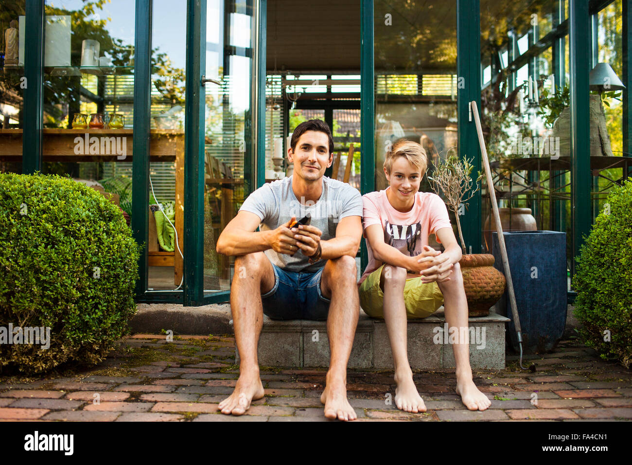 Full length portrait of father and son sitting outside house - Stock Image