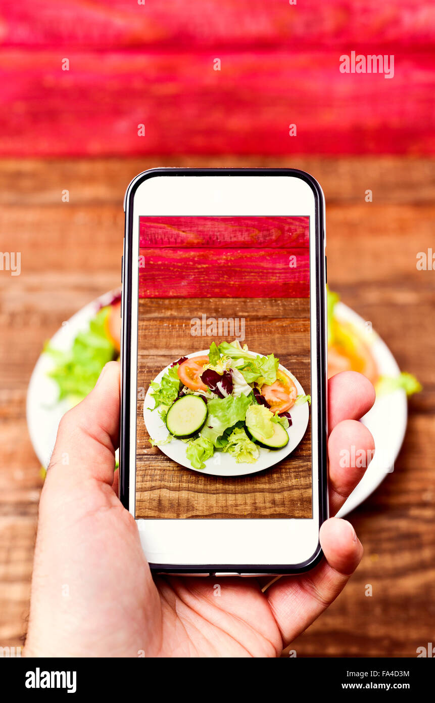 closeup of a young caucasian man taking a picture with his smartphone of a plate with salad placed on a wooden table - Stock Image