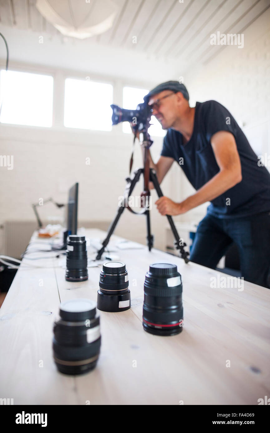 Mid adult photographer using SLR camera while various lenses on table in studio - Stock Image