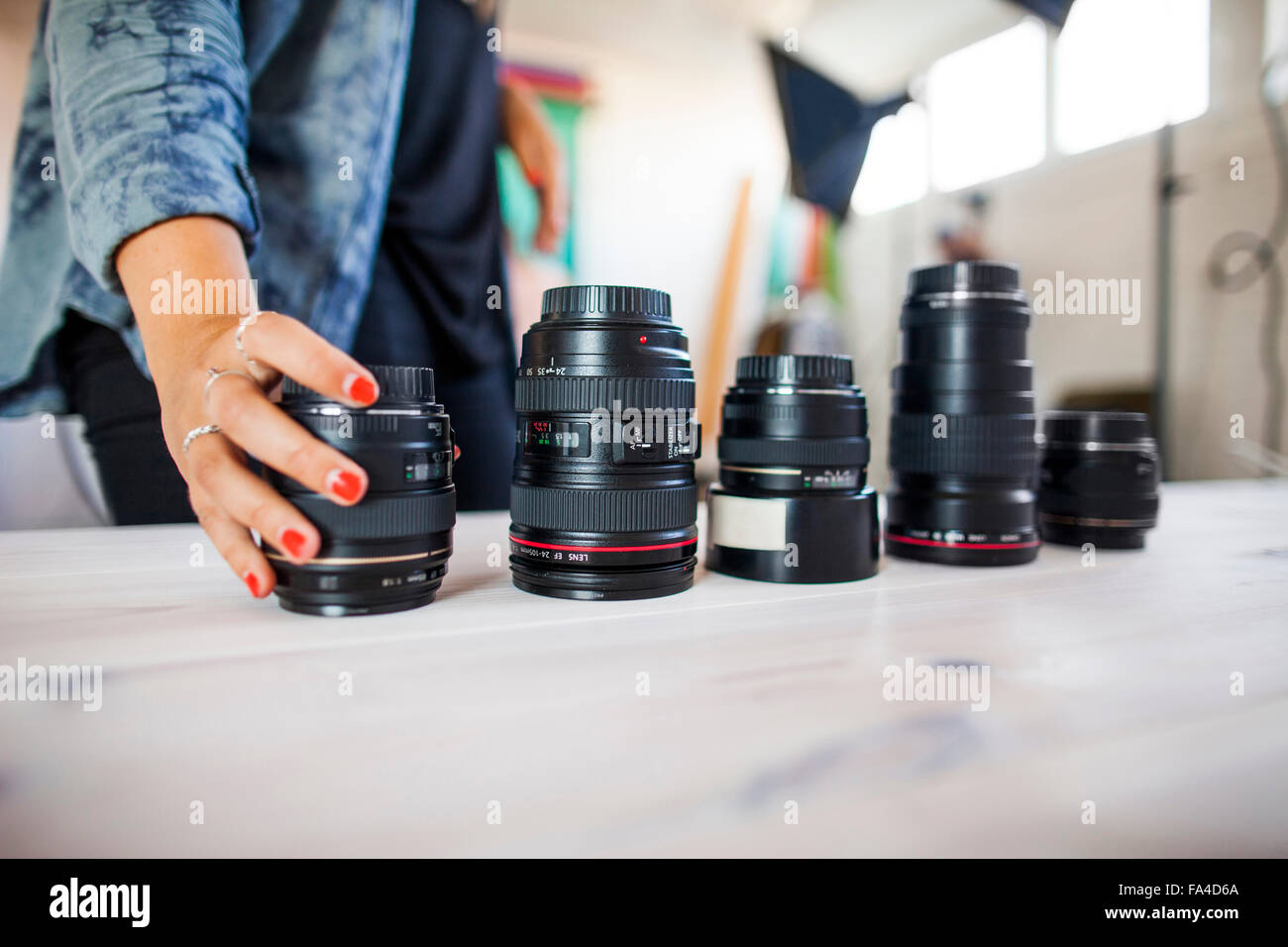 Midsection of photo assistant arranging various lenses on table in studio - Stock Image