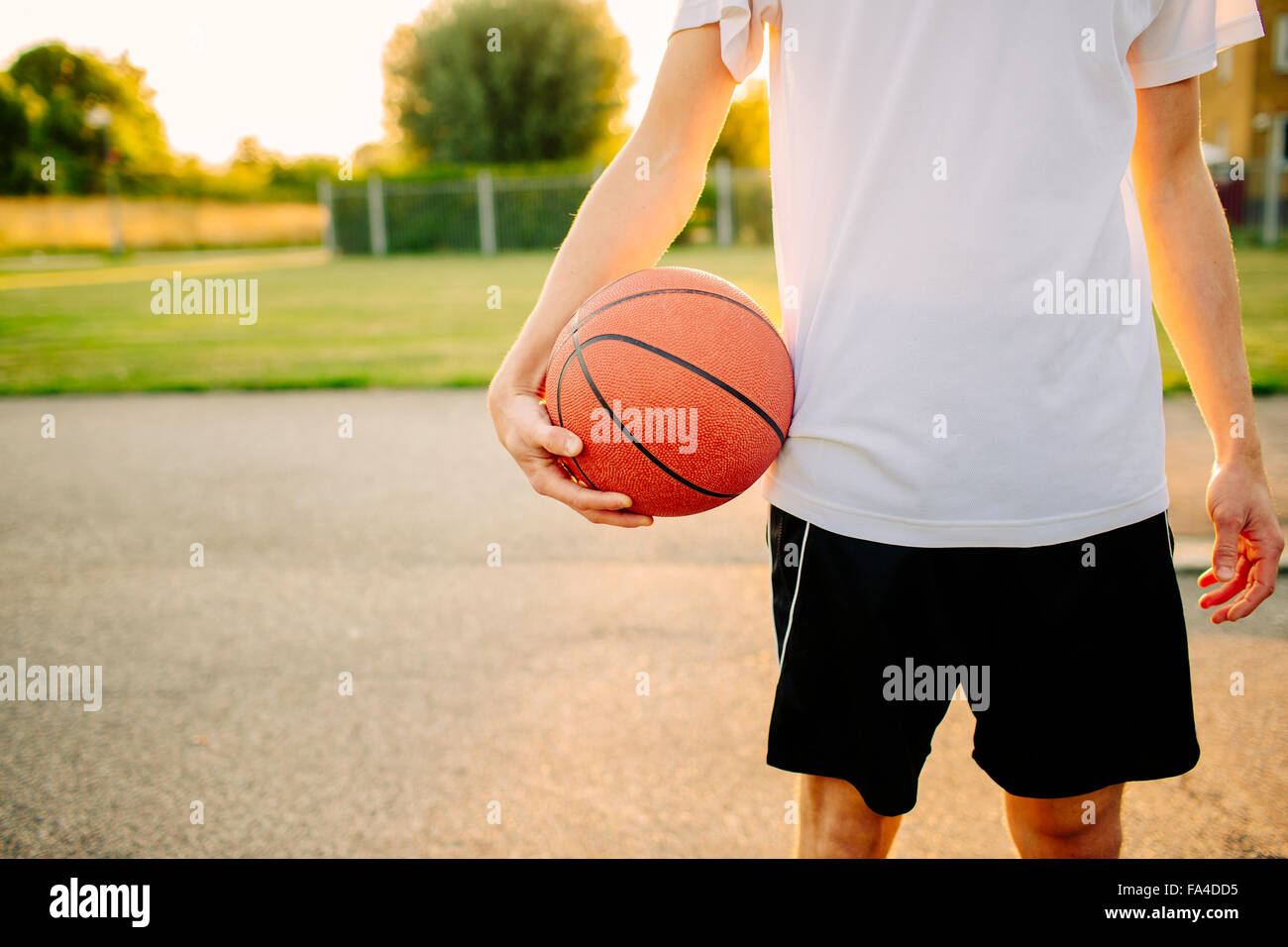 Midsection of man holding basketball at court in park - Stock Image