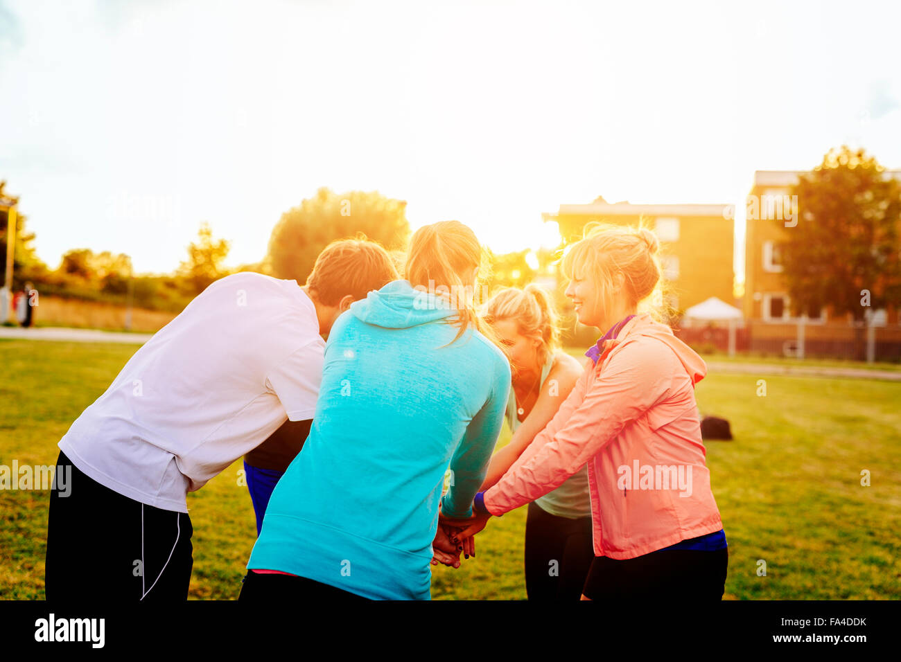 Sporty friends stacking hands in huddle at park during sunset - Stock Image