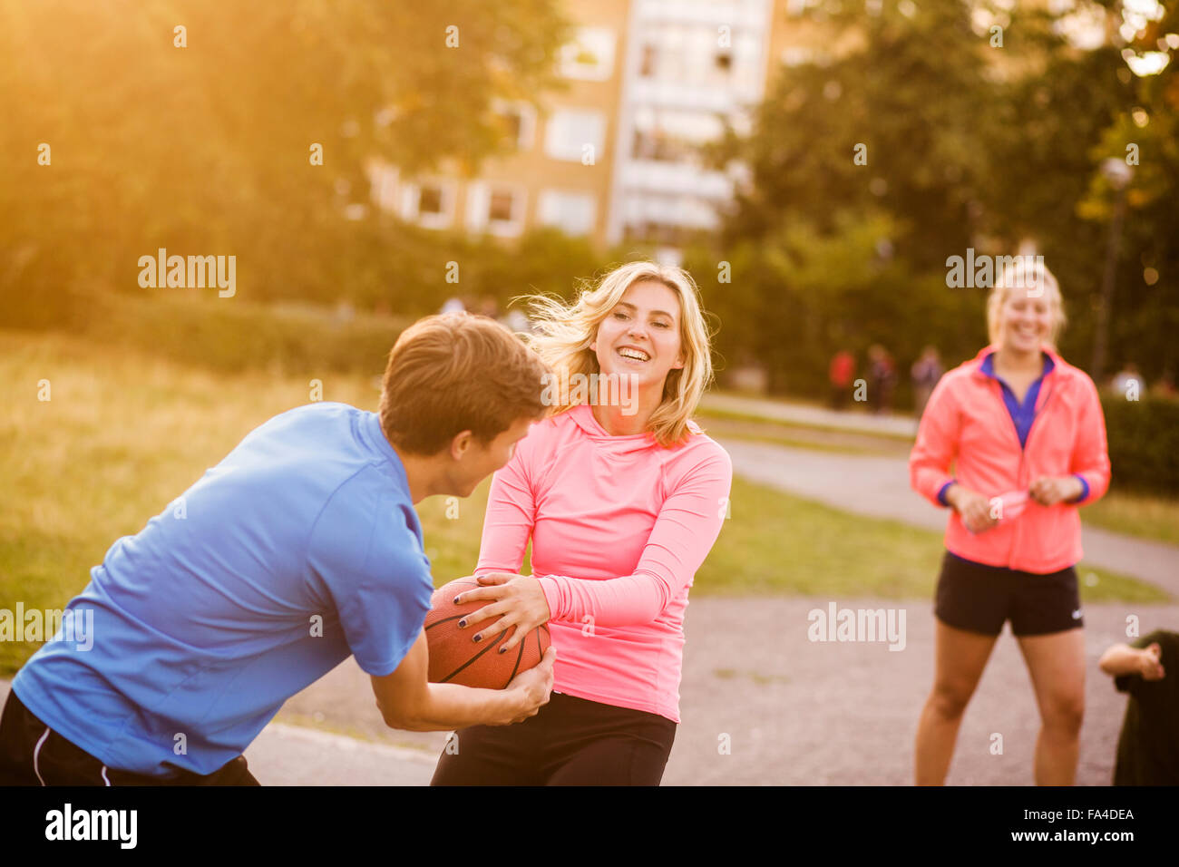 Happy man and woman snatching basketball at park - Stock Image