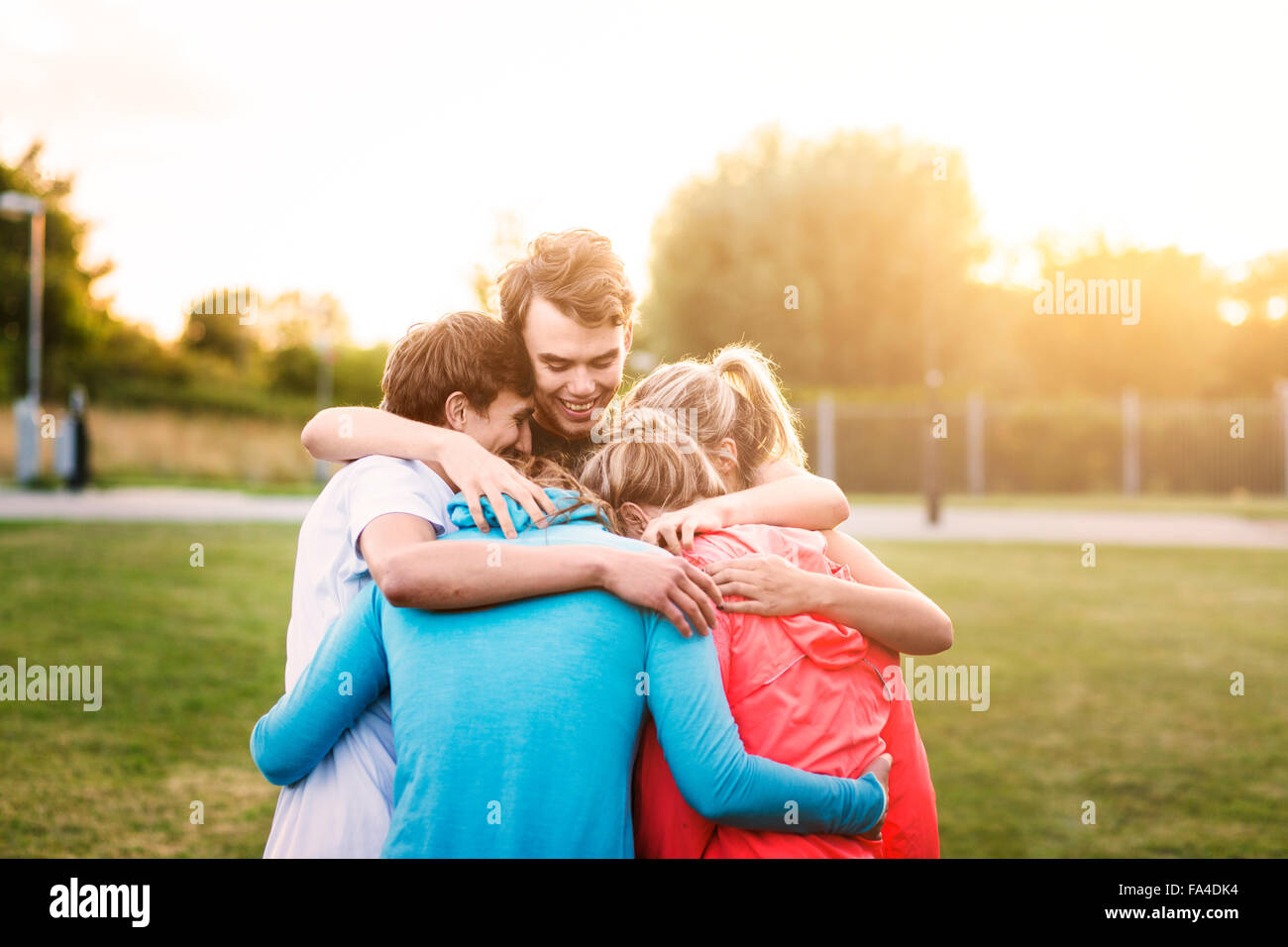 Male and female friends forming huddle at park during sunset - Stock Image