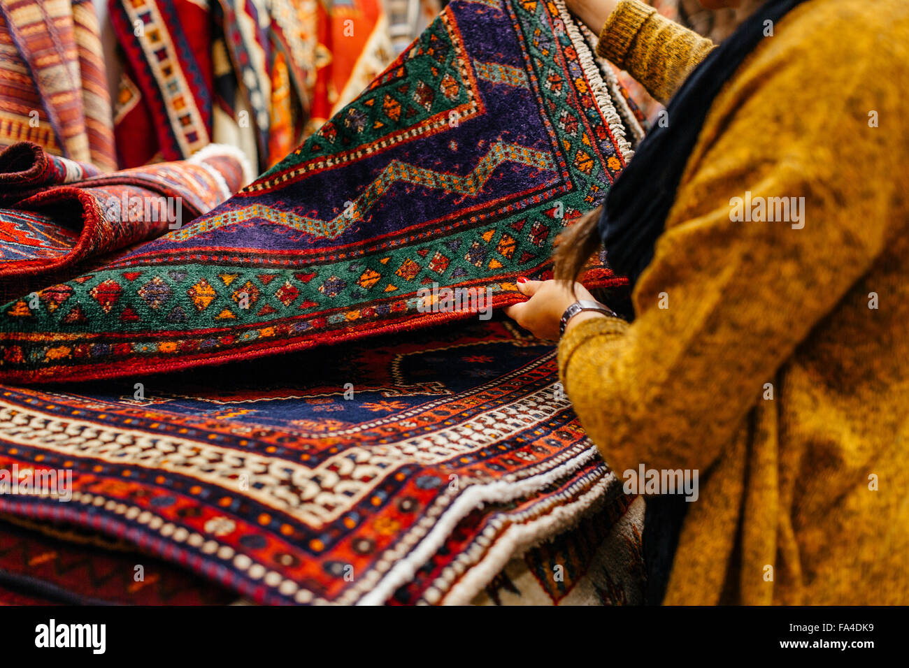 Midsection of young woman shopping for rugs in furniture warehouse - Stock Image