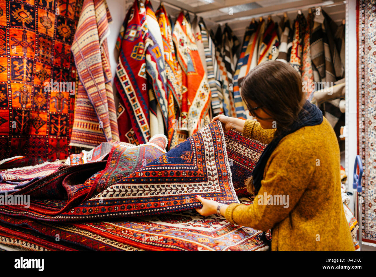 Young woman shopping for rugs in furniture warehouse - Stock Image