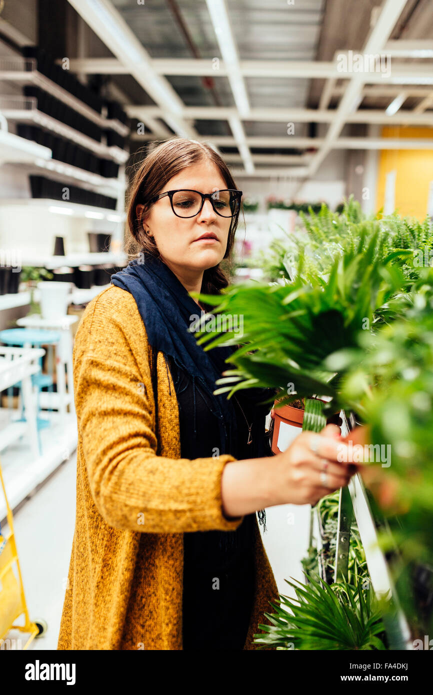 Young woman buying plants in garden center - Stock Image