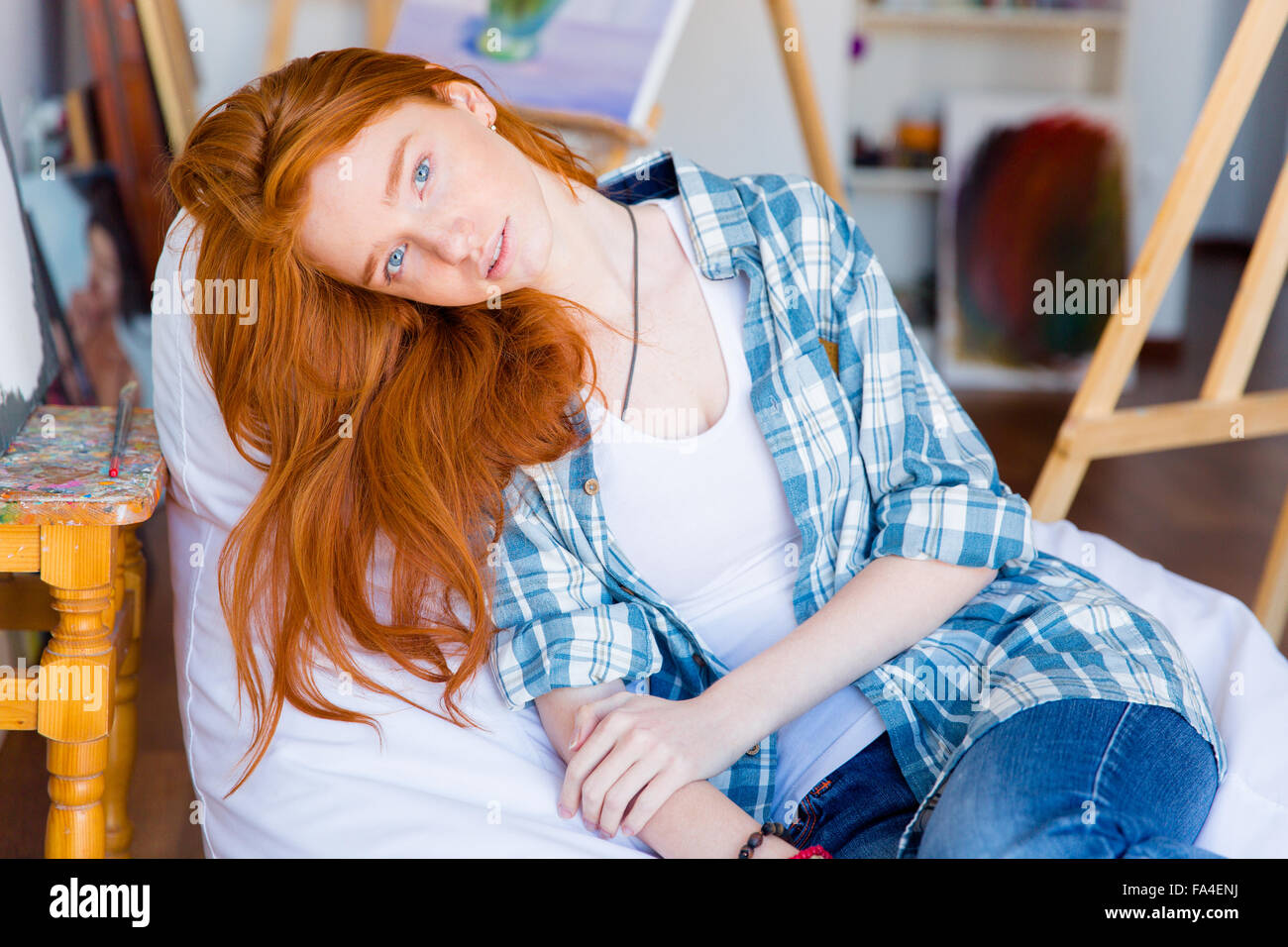 Relaxed pensive young female with long red hair lying on white beanbag in art studio - Stock Image