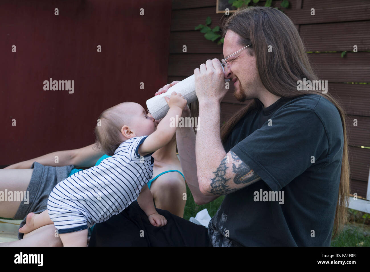 Baby boy and his father looking through a roll of paper towels from both ends, Munich, Bavaria, Germany - Stock Image