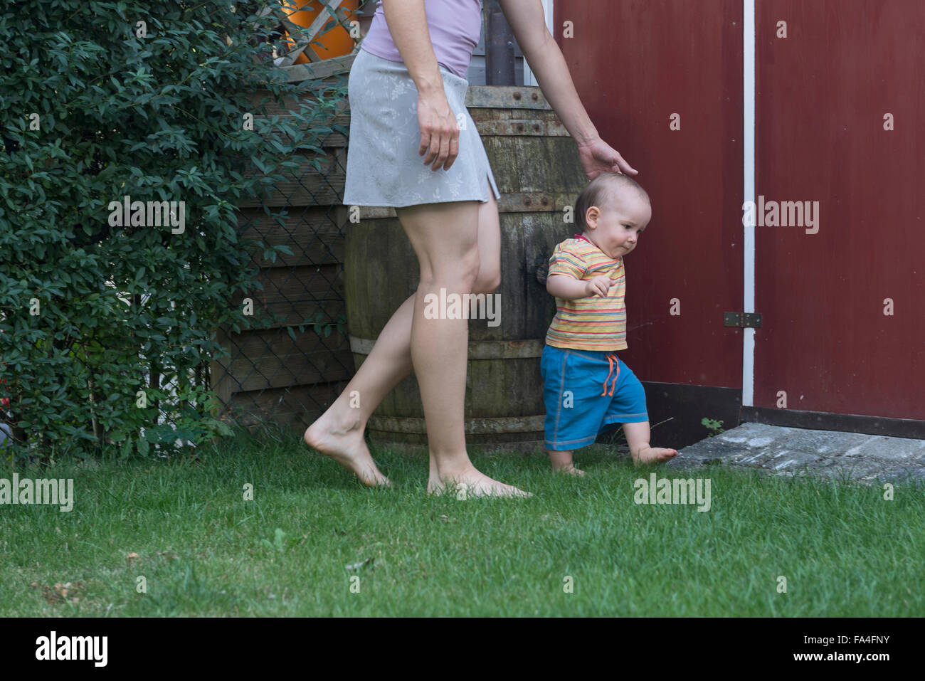Mother assisting her baby son walking upright, Munich, Bavaria, Germany - Stock Image