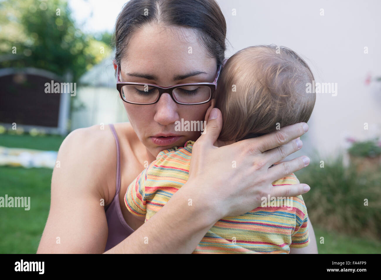 Mother comfort her baby son in a lawn, Munich, Bavaria, Germany Stock Photo