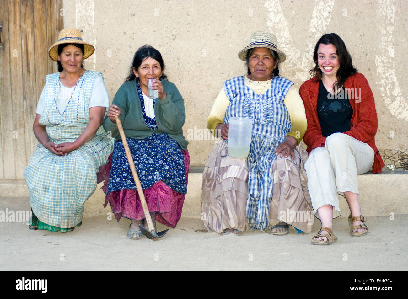 4 women, three Aymaran women local to Luribay, Bolivia, South America, sit smiling and drinking lemonade together. - Stock Image