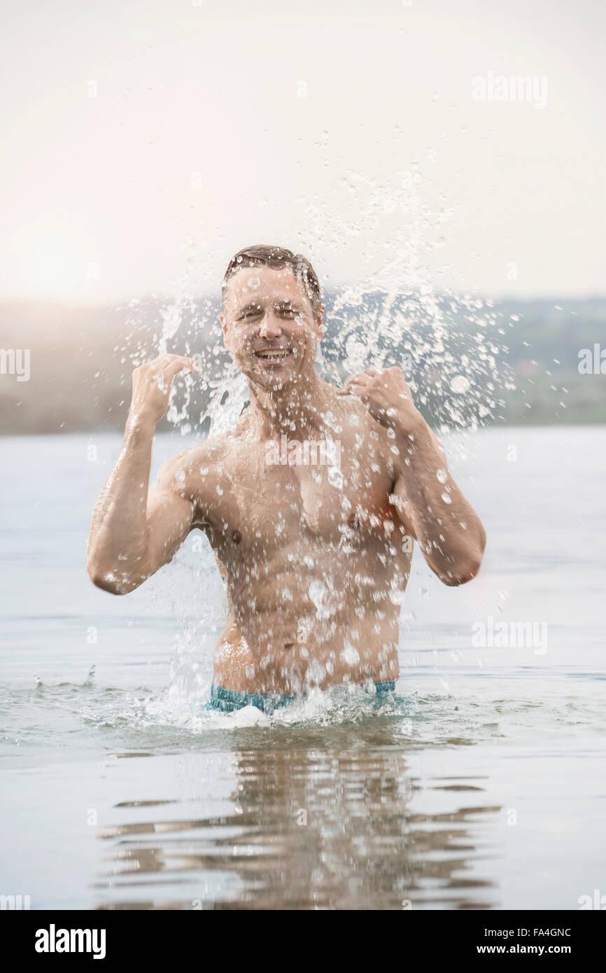 Mature man in lake with full of splash, Bavaria, Germany - Stock Image