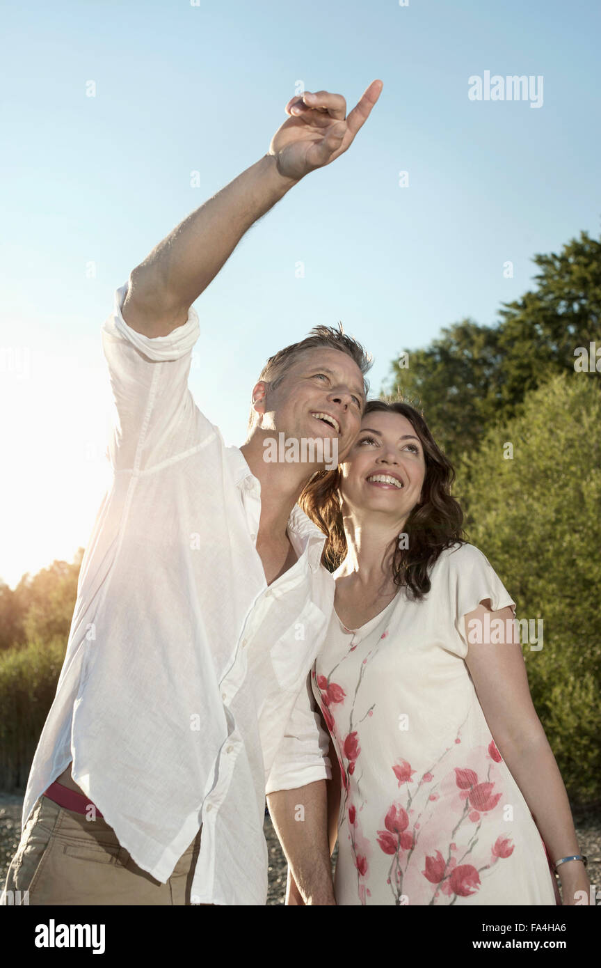 Mature man showing something to his wife at lakeside, Bavaria, Germany - Stock Image