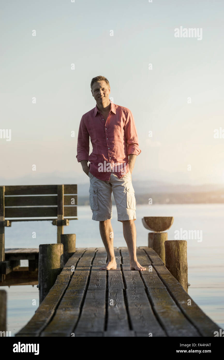 Mature man standing on wooden pier with hands on pockets, Bavaria, Germany - Stock Image