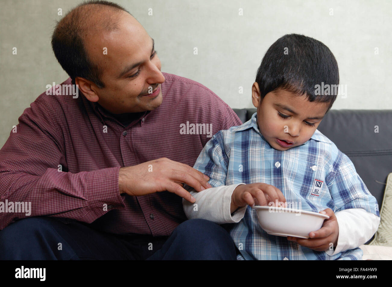 Single parent sitting with his young son while he eats his meal, - Stock Image