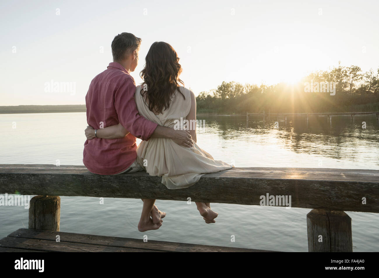 Mature couple sitting on pier looking at sunset, Bavaria, Germany - Stock Image