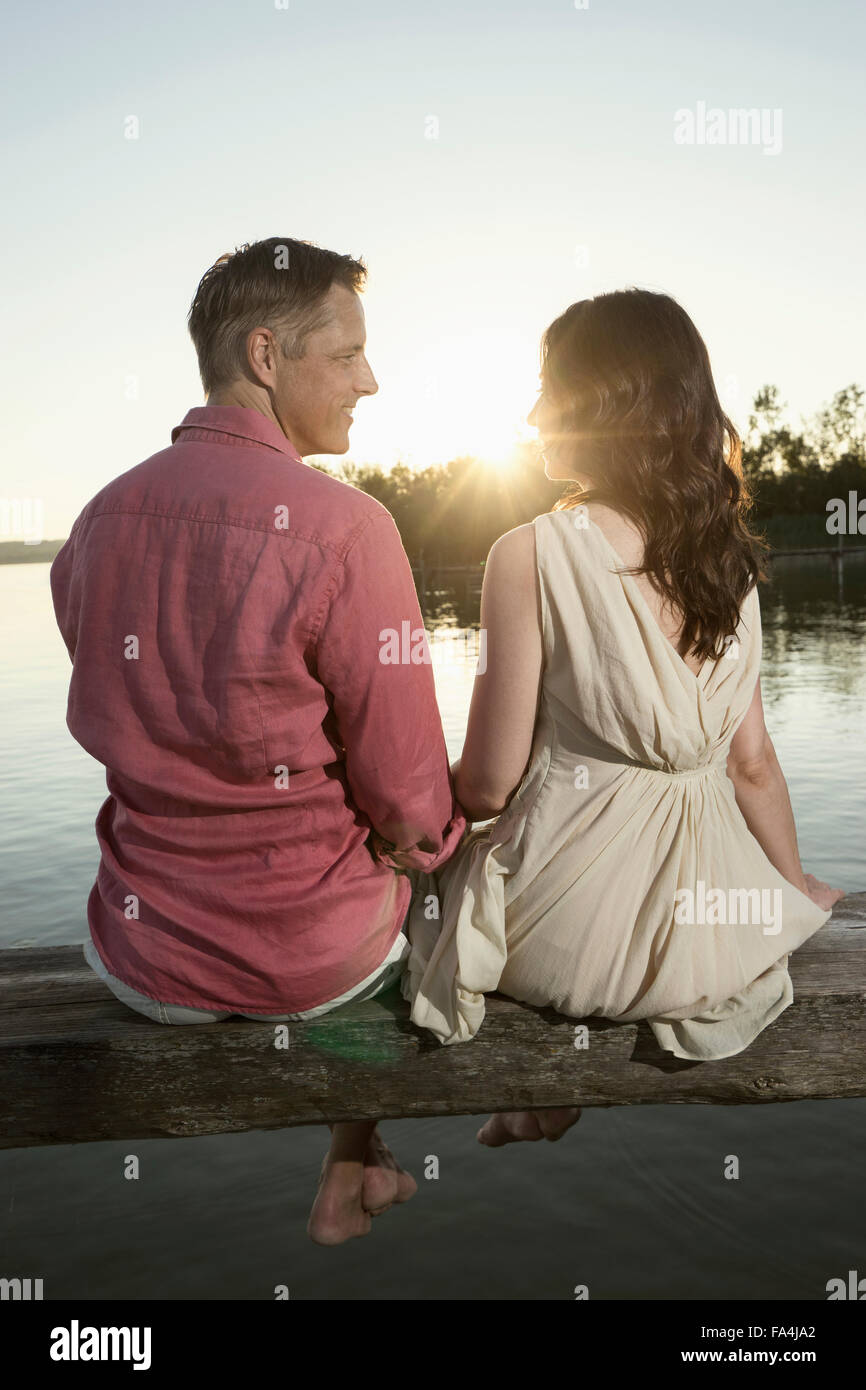 Mature couple looking at each other on pier at sunset, Bavaria, Germany - Stock Image