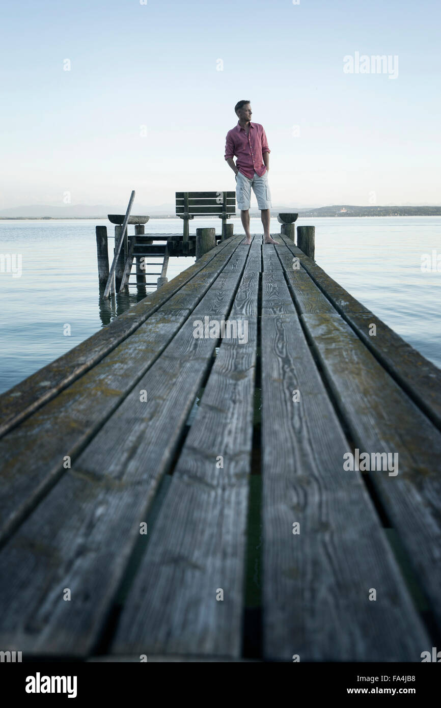 Mature man standing on wooden jetty and looking at distance, Bavaria, Germany, - Stock Image