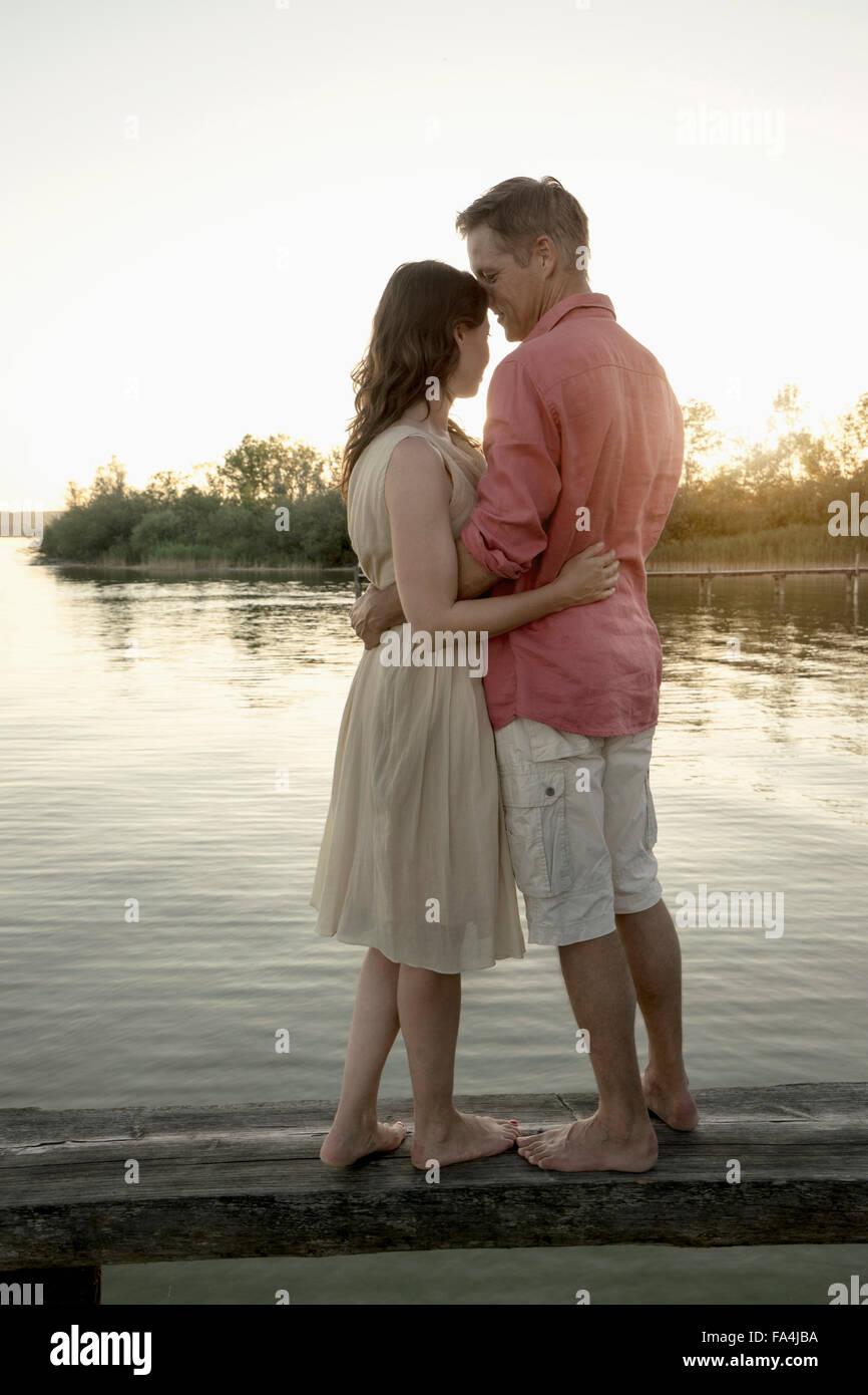 Mature couple hugging on pier at lake during sunset, Bavaria, Germany - Stock Image