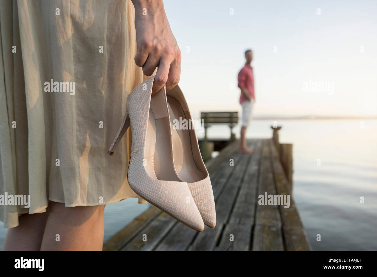 Mature man waiting for her wife on pier at lake, Bavaria, Germany - Stock Image