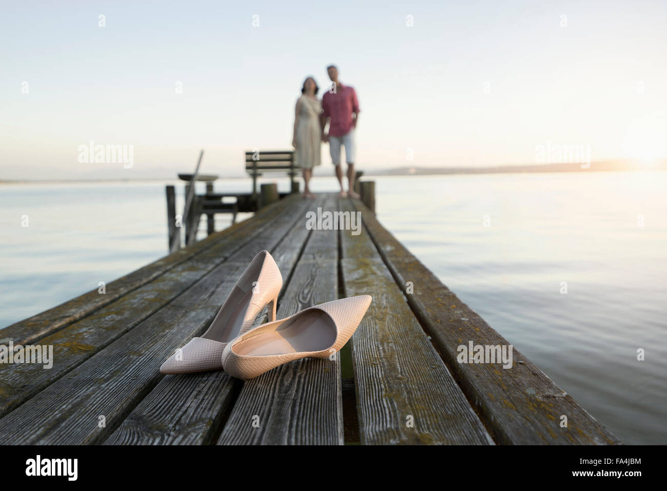 Dress shoe with mature couple standing on pier, Bavaria, Germany - Stock Image