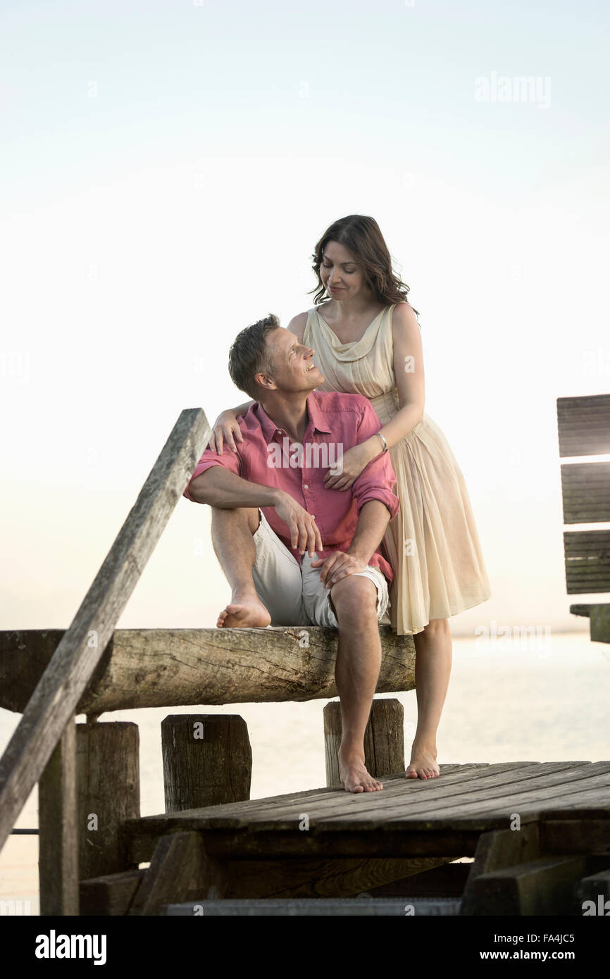 Mature couple looking at each other and smiling on pier, Bavaria, Germany - Stock Image