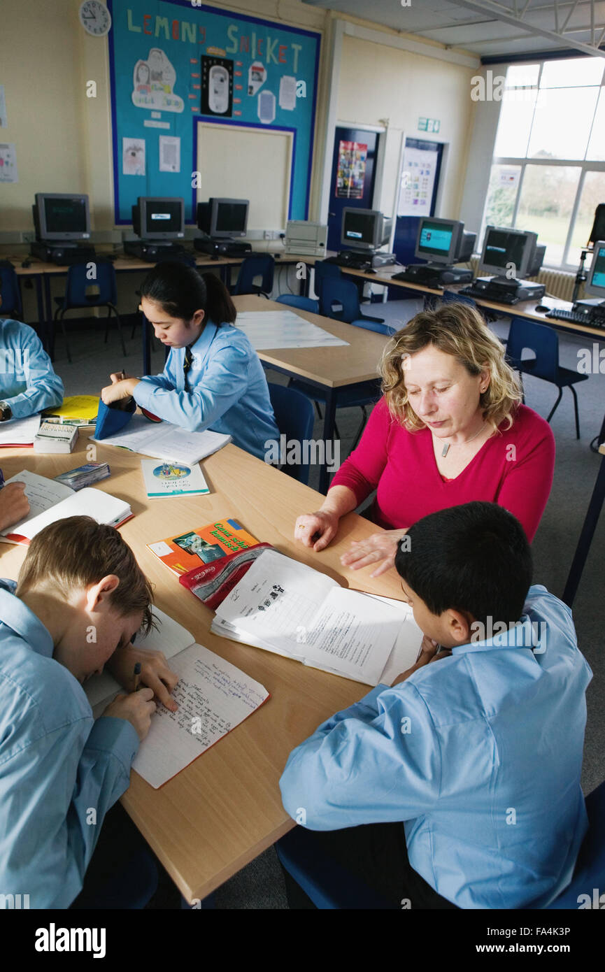 Secondary school students working around a desk with their teacher, - Stock Image
