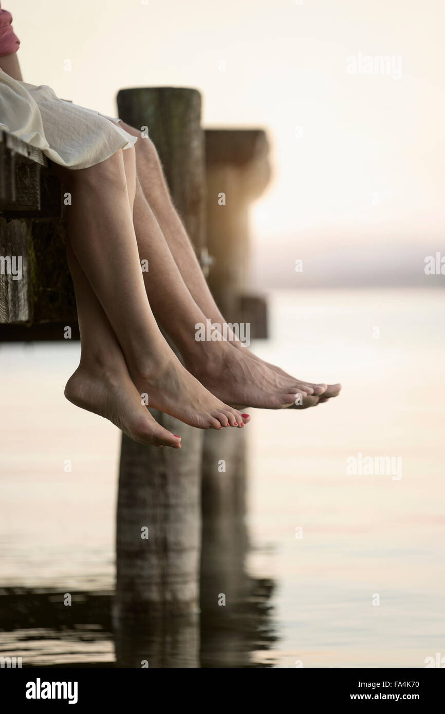 Couple legs dangling on pier, Bavaria, Germany - Stock Image