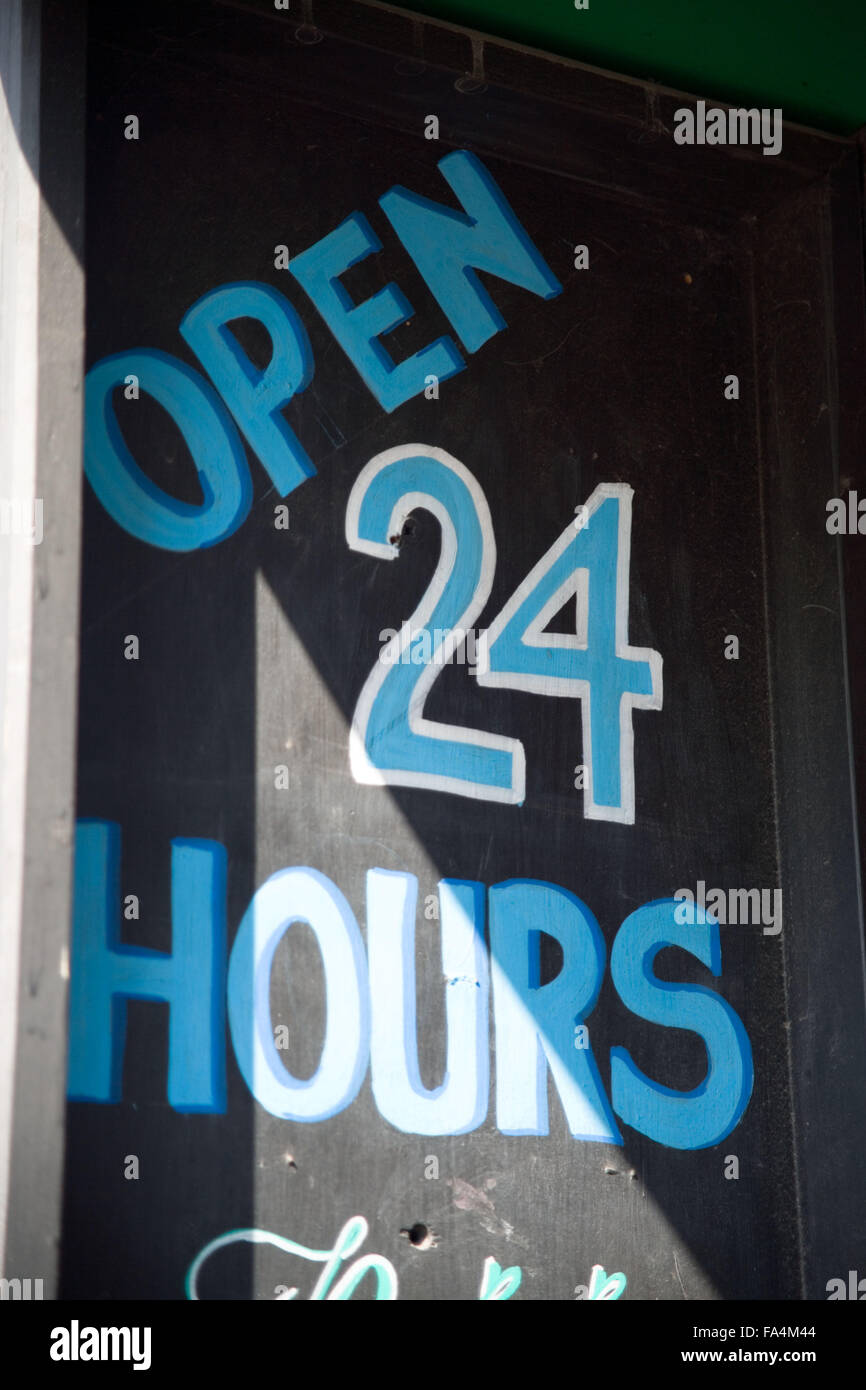 Sign in front of shop selling alcoholic drinks 24 hours a day, - Stock Image