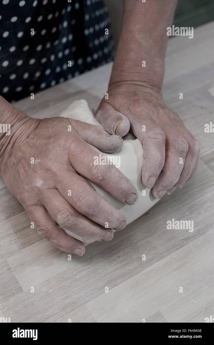 Close-up of female potter kneading clay on workbench, Bavaria, Germany - Stock Image